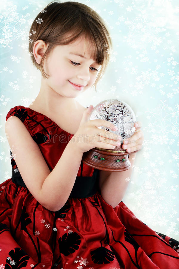 Child with Snow Globe. Happy little girl holding a snow globe stock images