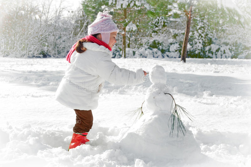 Child and snowman. Winter scene with child making a snowman