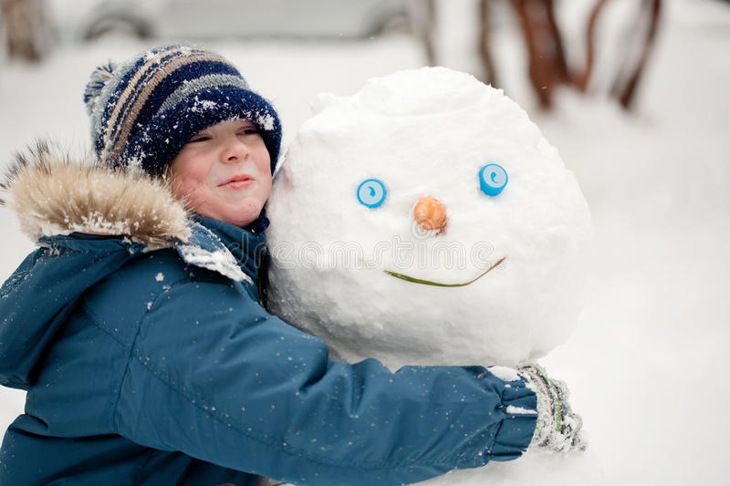 The child and the Snowman. Boy hugging a snowman. Winter, outdoors, close-up stock photos