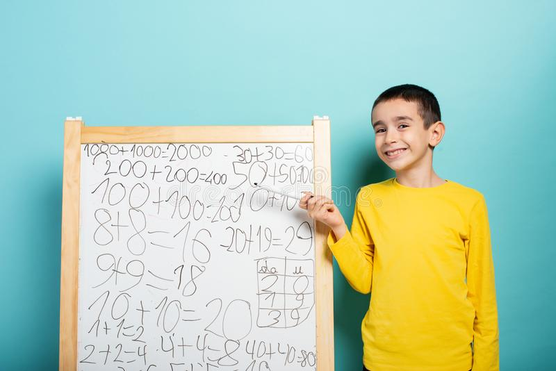 Child solves mathematical problem with abacus. Cyan background stock image