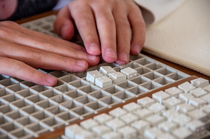 Child solving crossword on Braille alphabet. Child solving crossword puzzle game on Braille alphabet royalty free stock photography