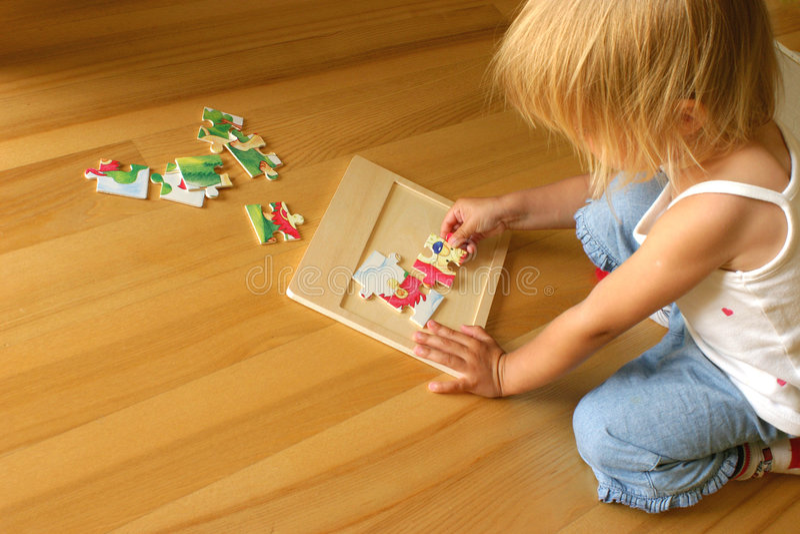 Child solving puzzle stock photo
