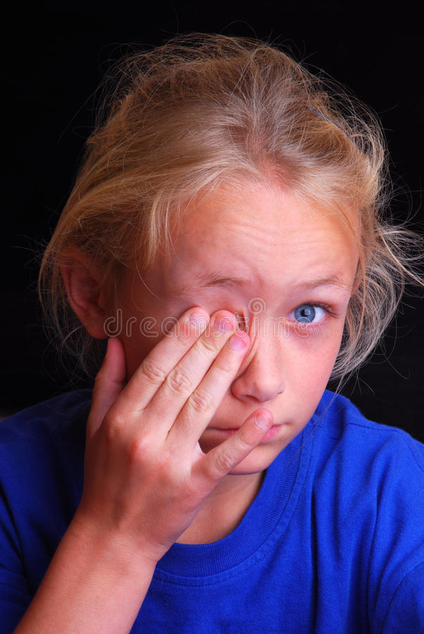 Child with sore eye. Portrait of a cute little Caucasian blond girl child covering her sore eye with her hand. Image on black studio background stock photos