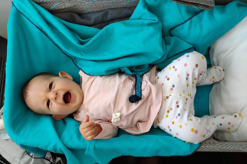 A child in a special cradle on the plane. Top view. Baby Yawns in bassinet lying at green plaid.  stock photo