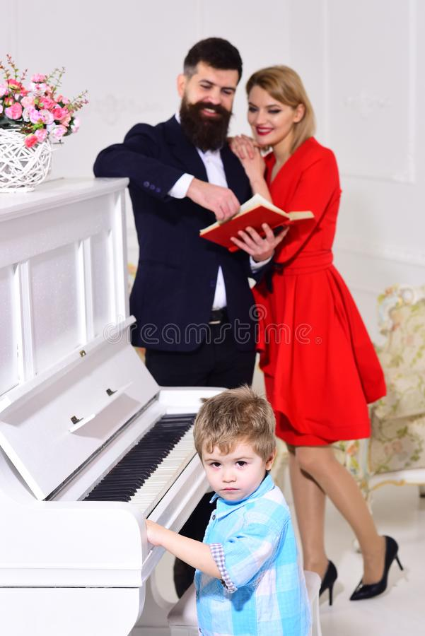Child stand near piano keyboard, white interior background. Musician education concept. Boy adorable try to play piano. Musical instrument, while parents royalty free stock photo