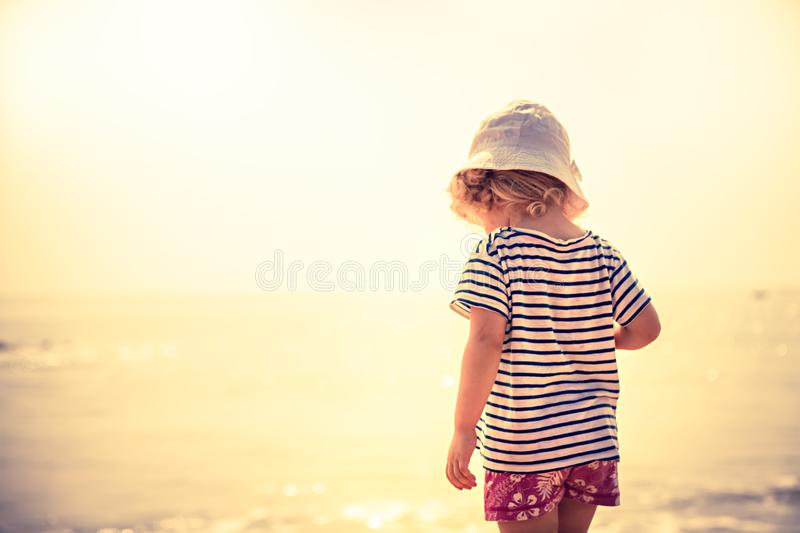 Child standing alone on beach with bright orange sunset sunlight during summer beach holidays concept happy childhood travel lifes stock photo