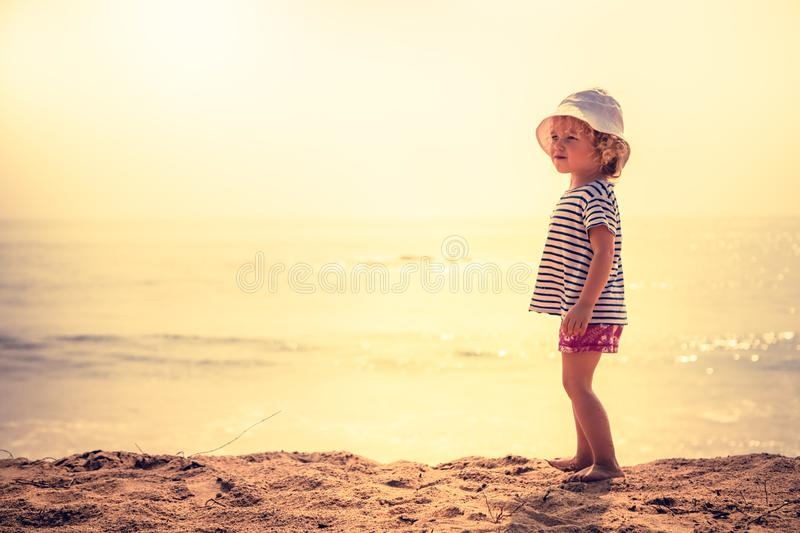 Child standing alone on beach with bright orange sunset sunlight during summer beach holidays concept happy childhood travel lifes stock images
