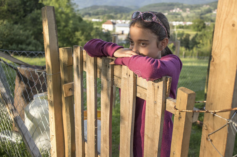 Child standing near vintage rural fence royalty free stock photos