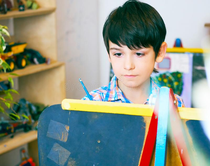 Child standing next to the easel. Kid boy learn paint by brush in class school. Kindergarten interior on background. Boy royalty free stock photography