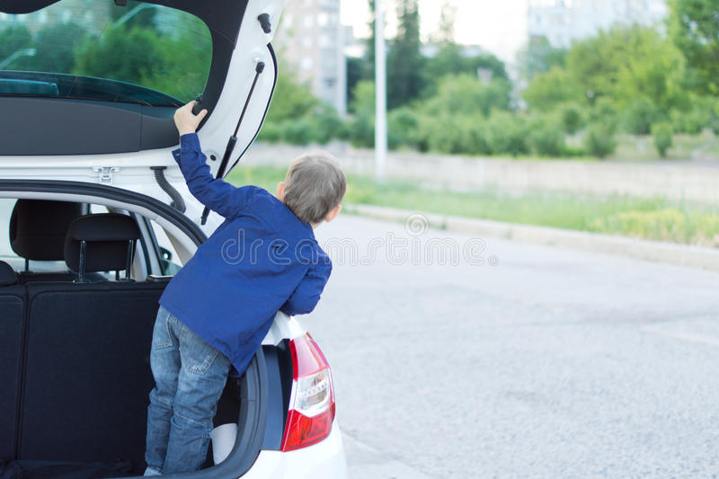 Child standing in the open trunk of a car royalty free stock photos