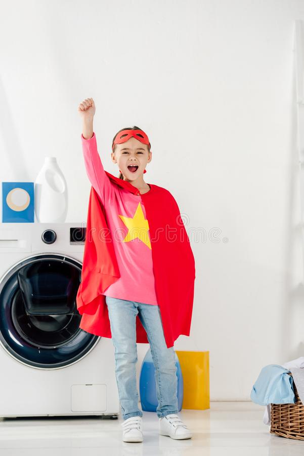 child standing in red homemade suit with star sign and showing celebrating royalty free stock images