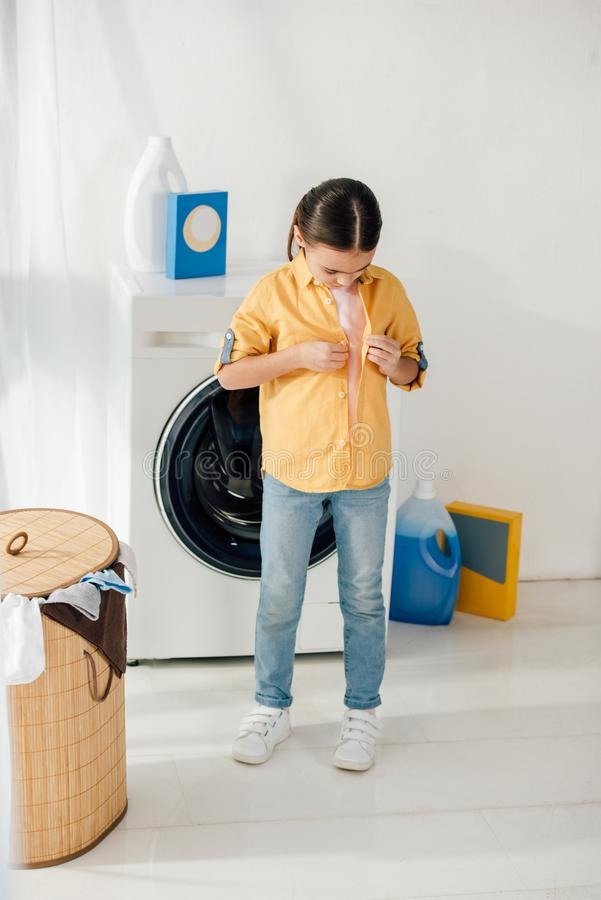 child standing and unzipping yellow shirt near washer and basket stock photos