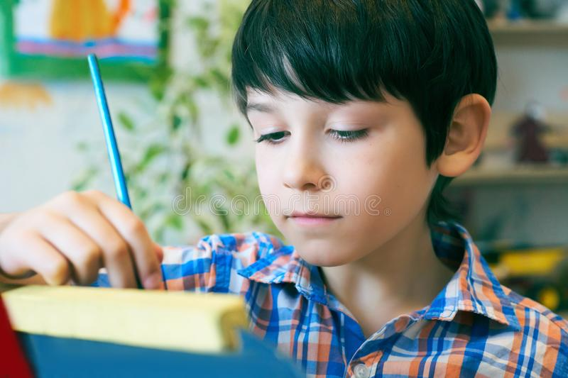 Child standingnext to the easel. Kid boy learn paint by brush in class school. Kindergarten interior on background. Boy royalty free stock photo