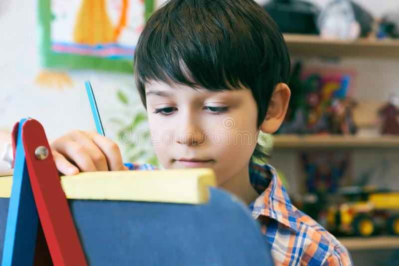 Child standingnext to the easel. Kid boy learn paint by brush in class school. Kindergarten interior on background. Boy royalty free stock image