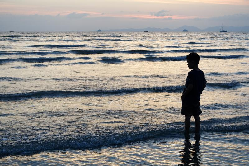A child stands in the sea of sunset in Krabi, Thailand. The sea surges up, and the distant sunset is the fishing boat that is heading home stock images