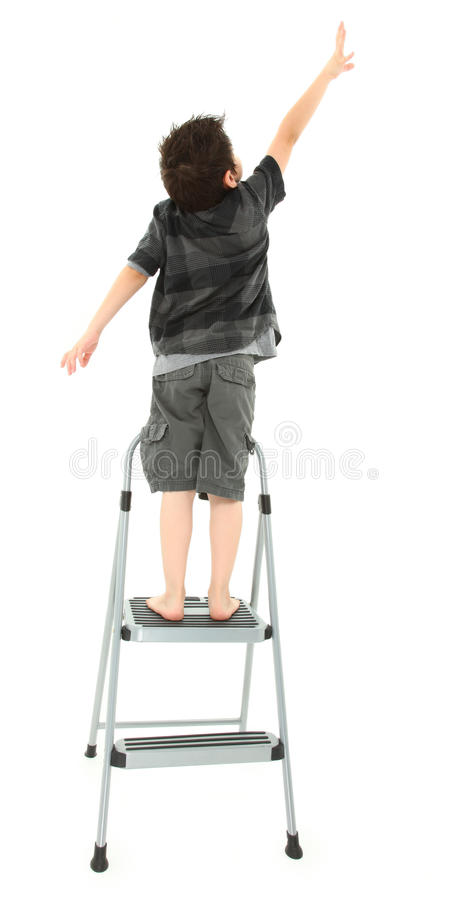 Child on Step Ladder Reaching Up. Young boy on step ladder reaching up over white background stock photography