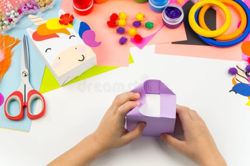 Child sticks hand craftwork unicorn. Unusual gift from paper box. Master class handmade. Favorite hobby. Kindergarten and school stock photos