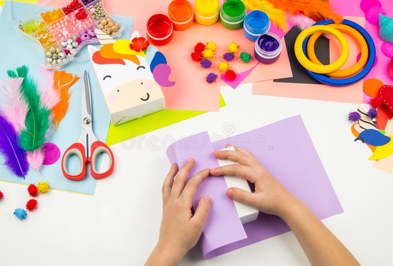 Child sticks hand craftwork unicorn. Unusual gift from paper box. Master class handmade. Favorite hobby. Kindergarten and school royalty free stock photo