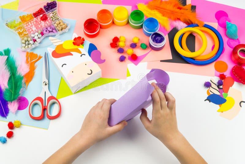 Child sticks hand craftwork unicorn. Unusual gift from paper box. Master class handmade. Favorite hobby. Kindergarten and school stock image
