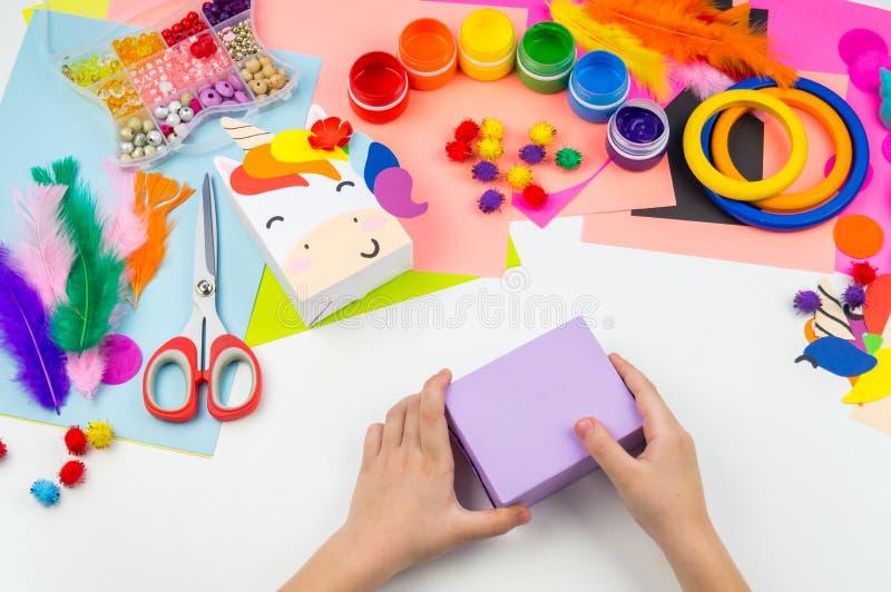 Child sticks hand craftwork unicorn. Unusual gift from paper box. Master class handmade. Favorite hobby. Kindergarten and school royalty free stock image
