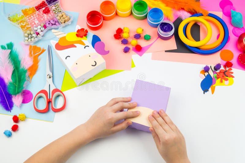Child sticks hand craftwork unicorn. Unusual gift from paper box. Master class handmade. Favorite hobby. Kindergarten and school royalty free stock photography