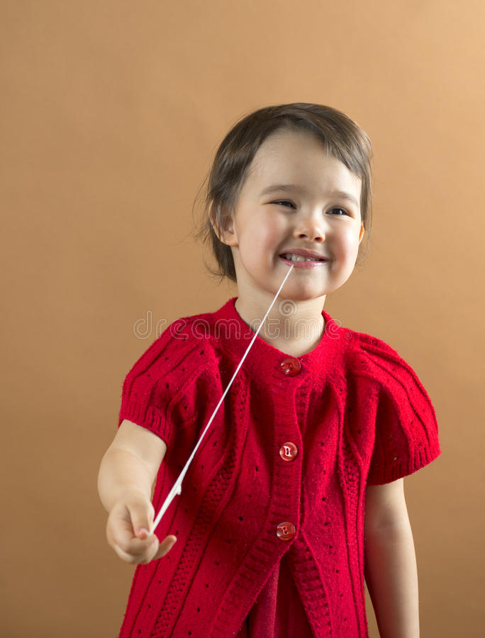 Child stretching a chewing gum from her mouth royalty free stock photography