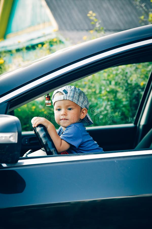 Little boy driving a car looking out the window stock photography
