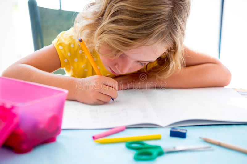 Child student kid girl writing with homework on desk. Table royalty free stock photography