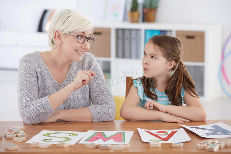 Child studying alphabet with teacher stock images