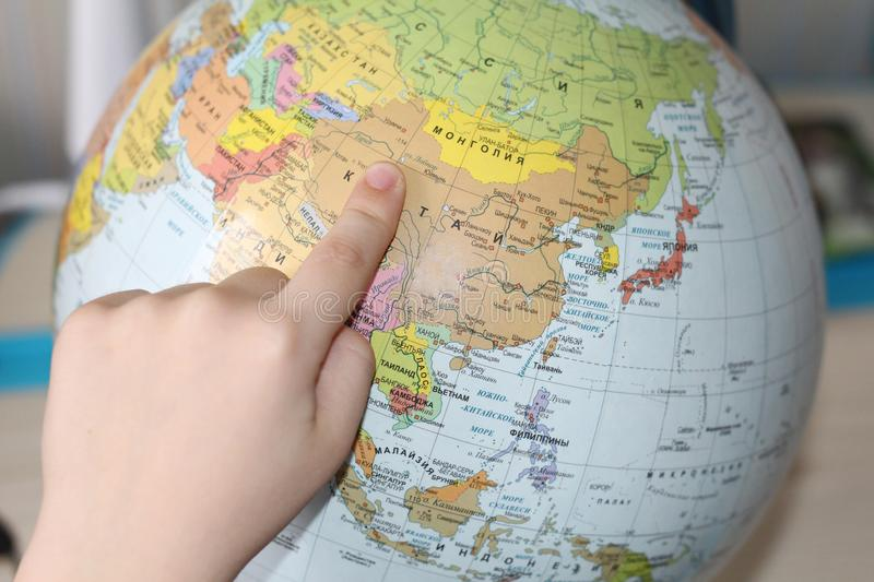 The child is studying geography. Finger pointing to the globe stock photos