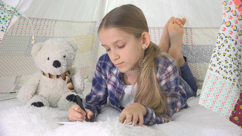 Child Studying, Student Kid using Tablet, Writing School Homework, Girl Playing.  royalty free stock images