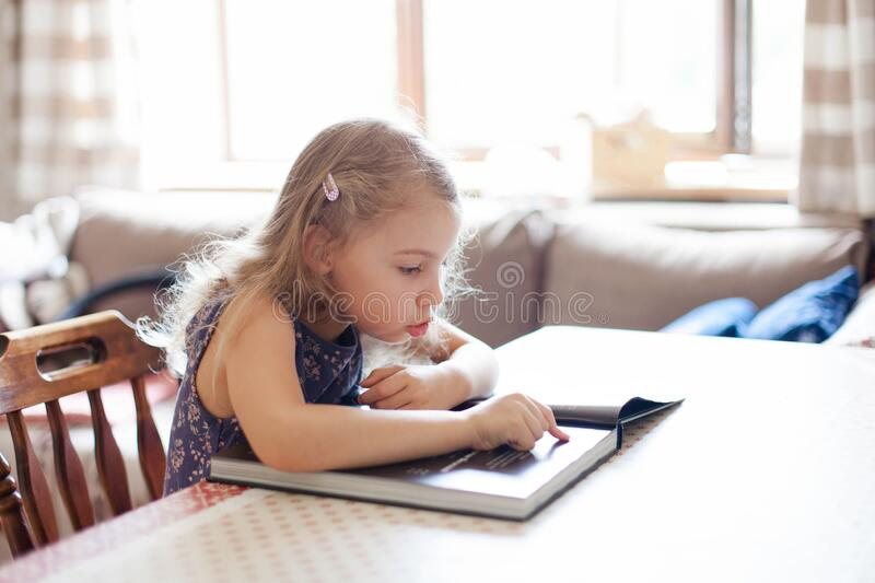 Child is studying to read at home. Kid is reading first book in cozy living room. Cute little girl is sitting at table stock photo