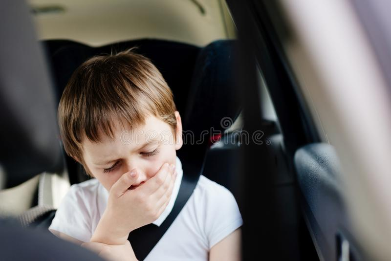 Child suffers from motion sickness in car. Child in the backseat of a car sitting in children safety car seat covers his mouth with his hand - suffers from stock photography