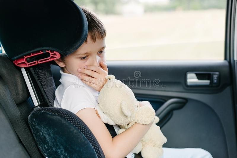 Child suffers from motion sickness in car. Child in the backseat of a car sitting in children safety car seat covers his mouth with his hand - suffers from royalty free stock images