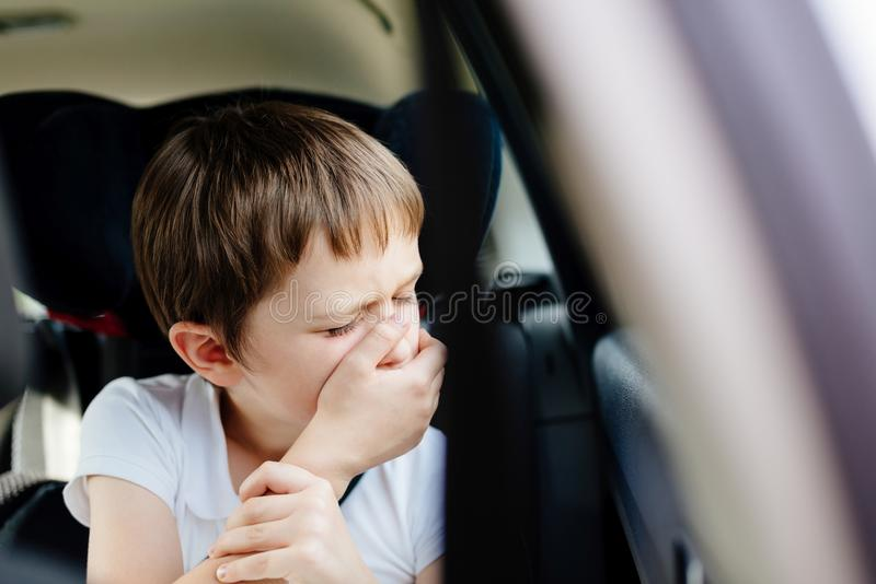 Child suffers from motion sickness in car. Child in the backseat of a car sitting in children safety car seat covers his mouth with his hand - suffers from royalty free stock photography