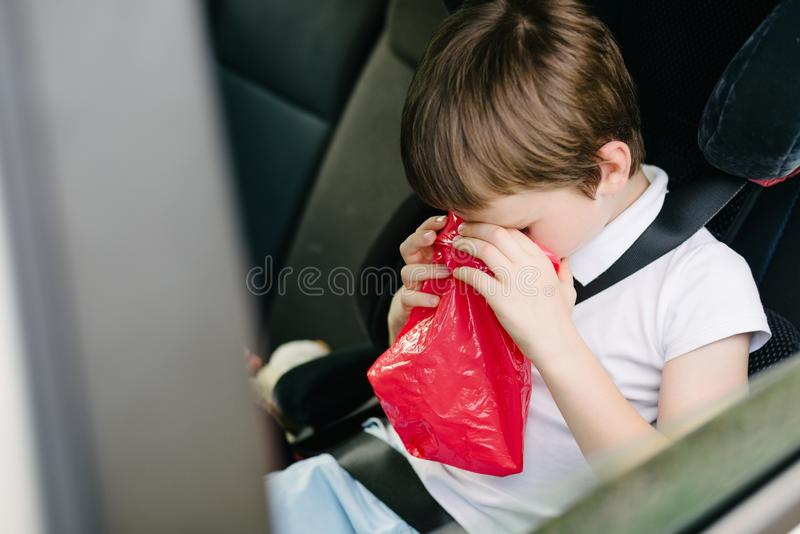 Child suffers from motion sickness in car. Child in the backseat of a car sitting in children safety car seat covers his mouth with his hand - suffers from royalty free stock photo