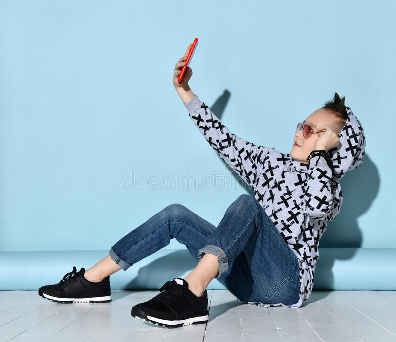 Child in sunglasses, jeans and hoodie, sneakers. Taking selfie by red smartphone, sitting sideways on white floor. Blue background. Teenage child in sunglasses royalty free stock photo