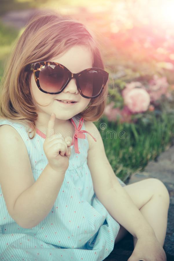 Child in sunglasses sitting in park on floral environment royalty free stock image