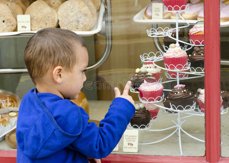 Child at sweet cake shop. Child looking through the window into sweet cake shop or bakery pointing to cakes royalty free stock photography