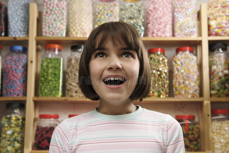 Child in sweet shop. Young girl smiling in awe at rows of sweets royalty free stock photography