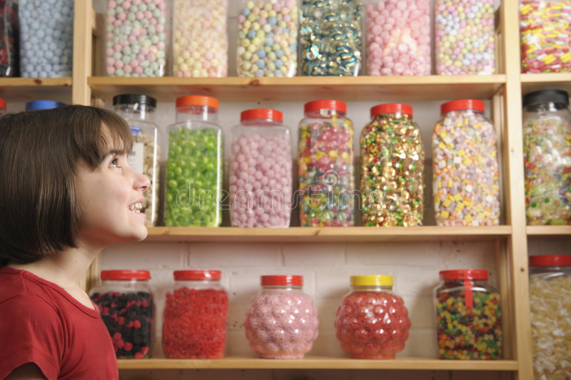 Child in sweet shop. Young girl smiling at camera in sweet shop stock photography