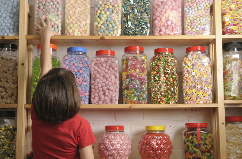 Child in sweet shop. Child reaching for sweet jar on top shelf royalty free stock photos