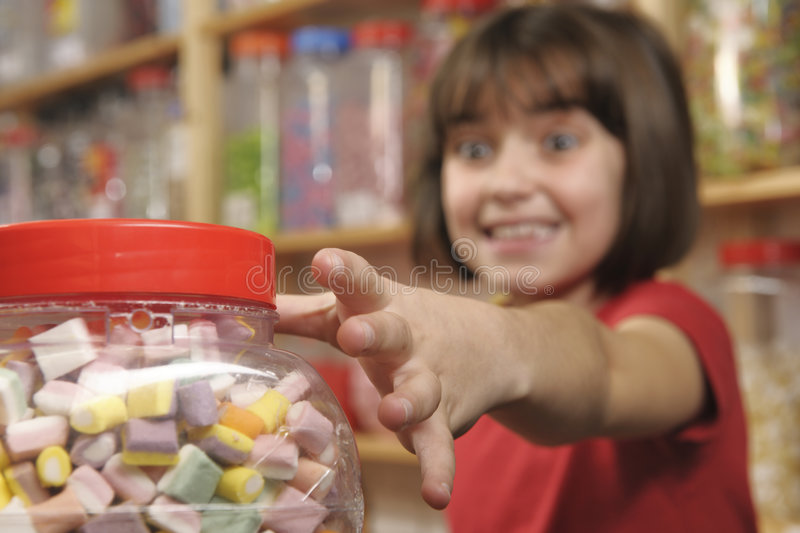 Child in sweet shop. Young girl grabbing a jar of sweets in shop royalty free stock photos