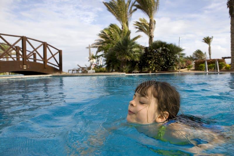 Child swimming. Fun in a swimming pool royalty free stock photo