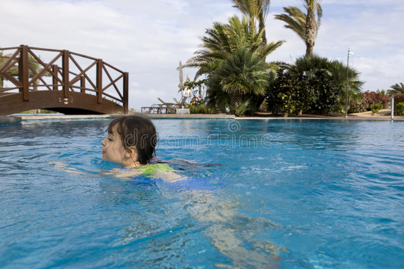 Child swimming. Fun in a swimming pool royalty free stock photography