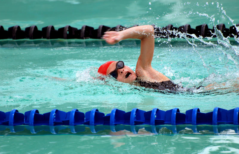 Child swimming. Little Caucasian girl child with black goggles and red cap swimming freestyle in the pool stock photos