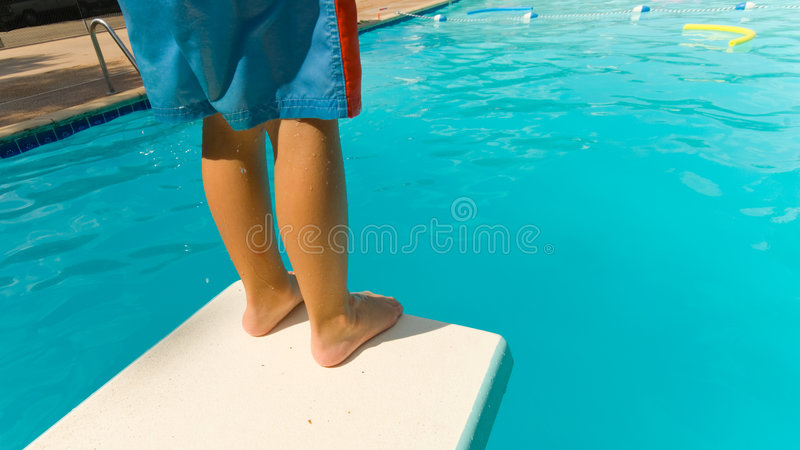 Child Swimming. Young boy standing on the end of a diving board at a swimming pool - seems to be a little apprehension stock photo