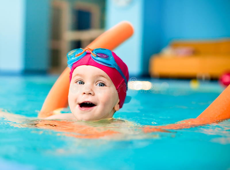 Child in a swimming pool. Happy little girl learning to swim with pool noodle stock photography