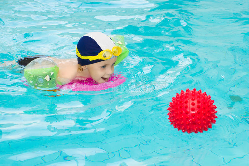 Child swimming pool, kid playing water ball, boy indoor training stock photo