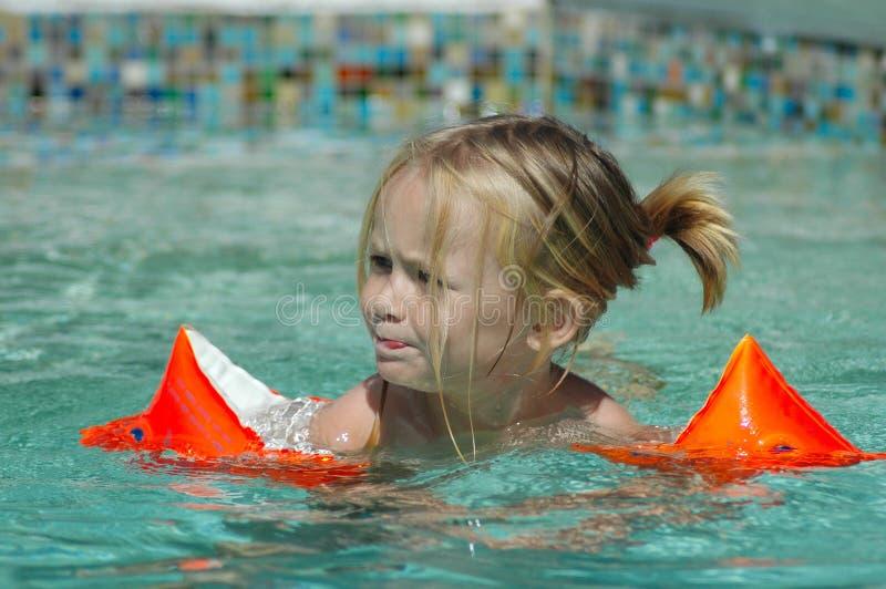 Child swimming in pool stock photo